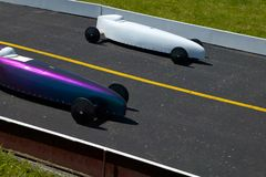 Two cars competing in a soap box derby race. Two cars competing in an American soap box derby race between two unpowered vehicles raced off a ramp in speed Royalty Free Stock Image