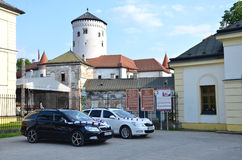 Two cars dedicated for wedding guests decorated by white ribbon on car park in front of the Budatin castle. Royalty Free Stock Photos