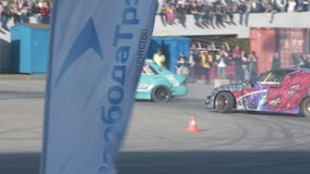 Two cars during drift competitions. NOVOSIBIRSK, RUSSIA - JUNE 03, 2016: Slow motion shot of two cars competing in drifting championship stock footage