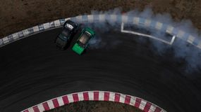 Two cars drifting battle on race track with smoke, Aerial view two car drifting battle.  stock photo