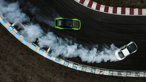 Two cars drifting battle on race track with smoke, Aerial view two car drifting battle.  stock image