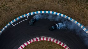 Two cars drifting battle on race track with smoke, Aerial view two car drifting battle.  royalty free stock image