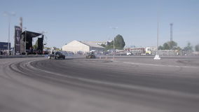 Two Cars Drifting on Summer Drift Race Making Smoke. Car fast drifting on the Big Car Summer Drift Competition in sunny hot day when people watching and making stock video footage