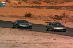 Two cars driving around race track. A tracked view of 2 cars driving around a race track stock footage