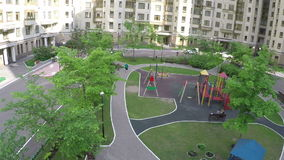 Two cars driving in the yard of multistorey houses, aerial view. Aerial shot of green yard of multistorey houses with playground and two cars driving stock video