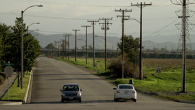 Two cars on an empty road. View of an empty road with two cars on it and a highway in the distance stock video footage