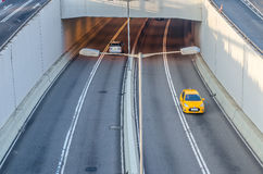 Two cars entering and outing the highway tunnel in morning. Stock Photo