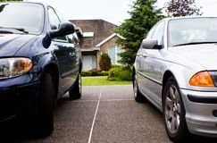Two cars, house  - suburban life. Two cars on driveway, house in distance - life in the suburbs Stock Photo