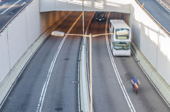 Two cars  and motorcycle outing the highway tunnel in morning. Stock Images