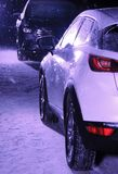 Two cars opposites on the winter road at night. Black car against white car on the snow road at night royalty free stock photos