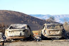 Cars burned out by recent wildfire. Two cars parked off the road, burned in the North Bay firestorm. Charred landscape in the background Royalty Free Stock Photo