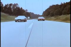Two cars racing on empty road stock video footage