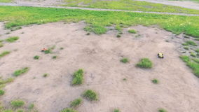 Two cars on the radio control rides on the field. Shooting from quadrocopter stock video