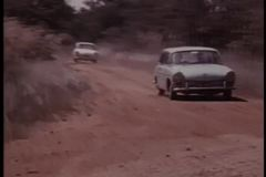 Two cars skidding off dirt road stock footage