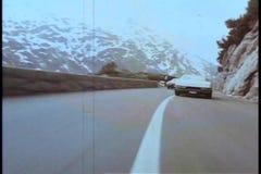 Two cars speeding through mountainside highway stock video