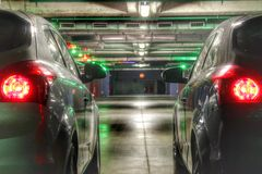 Two cars on the underground parking with red stop signals. stock photography