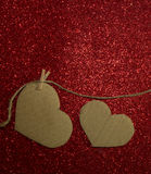 Two carton heart attached to the rope on red background Stock Images