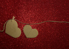 Two carton heart attached to the rope on red shining background Royalty Free Stock Images