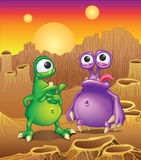 Two cartoon alien creatures on a background of ali. En planet landscape with three suns Stock Photography