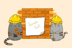 Two cartoon cats builders at the brick wall. Royalty Free Stock Photos