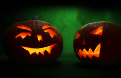 Two carved faces of pumpkins glowing on Halloween on green background Stock Photo