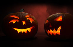 Two carved faces of pumpkins glowing on Halloween on red background Stock Image