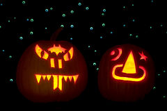 Two Carved Pumpkins. Lighted with candles, are placed in front of a backdrop of hundreds of googly eyes that are lit up with ultraviolet light. One pumpkin is stock photo