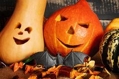 Two carved pumpkins, a bat and candy on a jute bag with a background of old planks. royalty free stock photos
