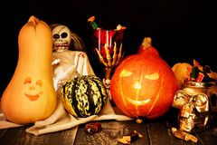Two carved pumpkins with a cup of skeleton and a skull full of candy. stock photography