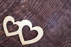 Two carved wooden hearts are lying diagonally on dark painted diagonal textured planks with copy space. royalty free stock photography