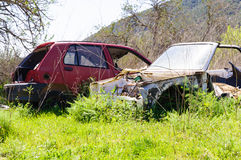 Two carwrecks on green grass. This photo shows to carwrecks on green grass Stock Photo
