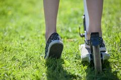 Two casters-rollers cycle and children feet riding on green grass Stock Photography