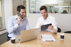 Two casual businessmen working together in modern office with la Royalty Free Stock Image