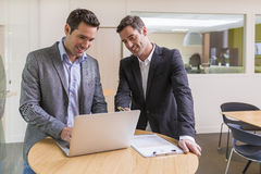 Two casual businessmen working together in modern office with la Stock Photo