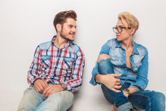 Two casual friends smile to each other while sitting Stock Image