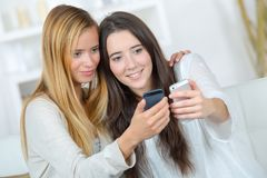 Two casual girls watching on line promotions on cellular. Two casual girls watching on line promotions on a cellular Royalty Free Stock Photography