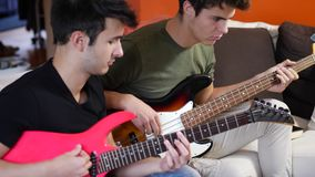 Young men playing electric guitars. Two casual guys posing on sofa and playing electric guitar and bass in band stock video