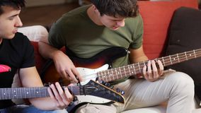 Young men playing electric guitars. Two casual guys posing on sofa and playing electric guitar and bass in band stock footage