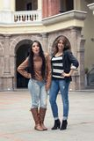 Two casual hispanic girls posing with hand on hip Stock Photos