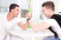 Two casual men arm wrestling. With face expression Royalty Free Stock Images