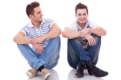 Two casual men sitting on a white background. One looking at the camera and the other looking at his friend Stock Photo