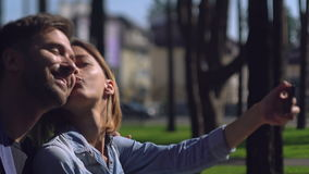 Two casual people play the fool using mobile phone. Attractive couple friends take selfie photo in the city. Adult man and woman have fun in city. Girl showing stock video footage