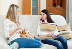 Two casual women gossiping on sofa Stock Image