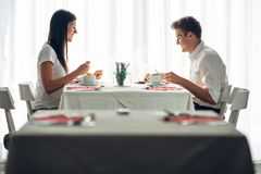 Two casual young adults having a conversation over a meal.Formal proposal,talking in a restaurant.Trying food,offers,special menu. Happy couple eating course in Stock Images