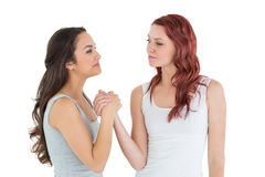 Two casual young female friends arm wrestling Stock Photo