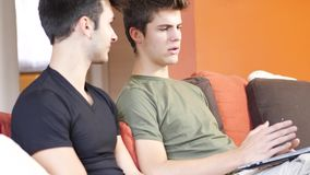 Two young male friends using laptop computer stock footage