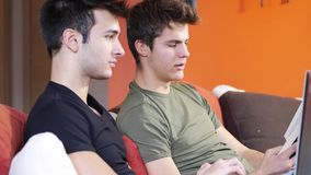 Two young male friends using laptop computer. Two casual young men friends relaxing on sofa at home sharing information and using laptop computer stock footage