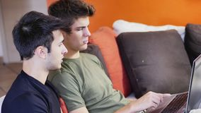Two young male friends using laptop computer. Two casual young men friends relaxing on sofa at home sharing information and using laptop computer Stock Photography