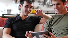 Two young male friends using tablet computer. Two casual young men friends relaxing on sofa at home sharing information and using tablet computer stock video