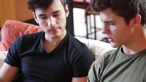 Two young male friends using tablet computer. Two casual young men friends relaxing on sofa at home sharing information and using tablet computer stock video footage